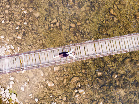 Photo pour Top drone view of woman with hands up in dress laying down on wooden bridge over river - image libre de droit