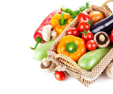 Foto de Fresh vegetables in wicker basket. Isolated on white background - Imagen libre de derechos