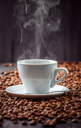 Photo pour Hot aromatic coffee drink in the white cup with saucer and spoon with beans background - image libre de droit