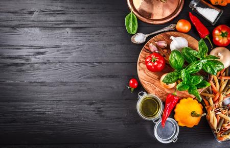 Foto de Vegetables and spices ingredient for cooking italian food on black wooden old board in rustic style - Imagen libre de derechos
