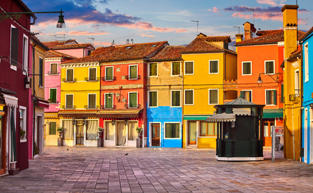 Bright coloured houses on Burano island Venice Italy with blue sky and clouds.