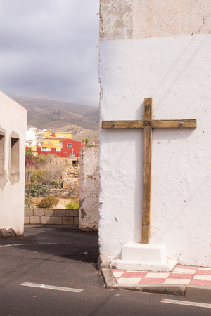 House with a white facade and an old wooden cross. Line of the road. View on the next houses of a village, built on a hill. Arico Viejo, Tenerife, Canary Islands, Spain.