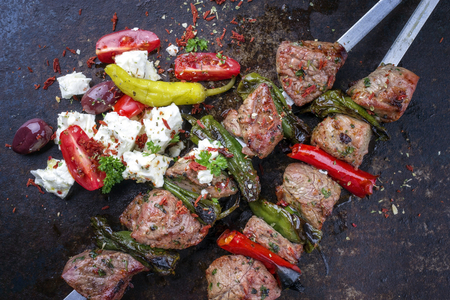 Traditional Greek Souvlaki with Feta and Vegetable on top of an old rusty metal sheet