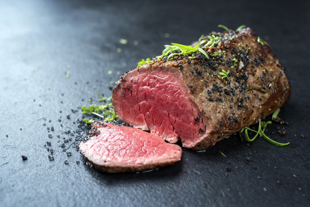 Photo pour Traditional barbecue dry aged wagyu fillet steak with herb and spice marinated as closeup on a black board - image libre de droit