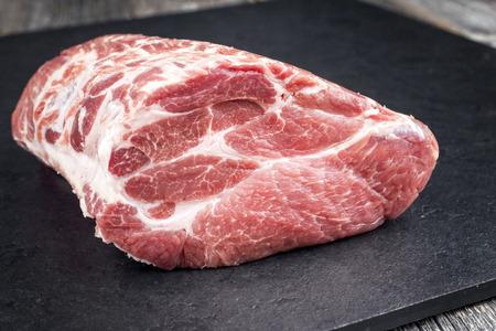 Photo pour Row piece of Bosten butt pork offered as close-up on a black board - image libre de droit