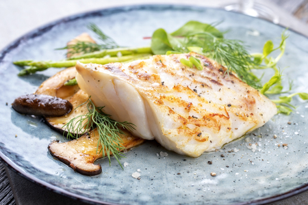 Photo pour Fried cod fish filet with green asparagus and mushrooms as close up on a plate - image libre de droit