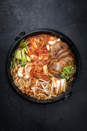 Photo pour Traditional Korean kimchi jjigae with grilled pork belly and ramen as top view in a pot - image libre de droit