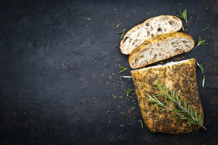 Photo for Traditional Italian ciabatta bread with herbs as top view on an old black board with copy space left - Royalty Free Image