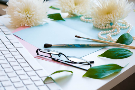 Notes of creative worker scattered on table. Work place of a creative person with a variety of colorful stationery objects. Business concept with copy space. Office desk table with glasses focus