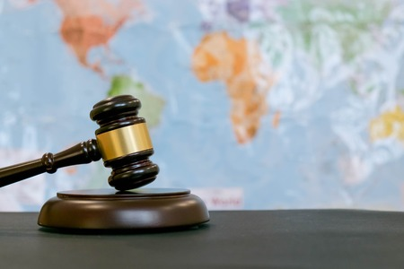 Photo pour Judge's gavel and over world map. Symbol for jurisdiction. Law concept a wooden judges gavel on table in a courtroom or law enforcement office on blue background. Copy space for text - image libre de droit