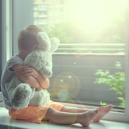 boy of two years sitting by the window and hugs a toy Bunny. rainy weather, waiting for dad to come home from work