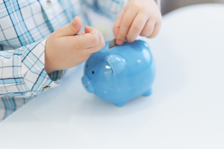 Photo pour three years old boy puts money in a piggy bank, piggybank concept. mantesori space in the house - image libre de droit