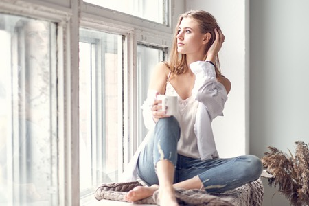 Foto de woman sitting on the windowsill and looking out the window. digital detox concept - Imagen libre de derechos