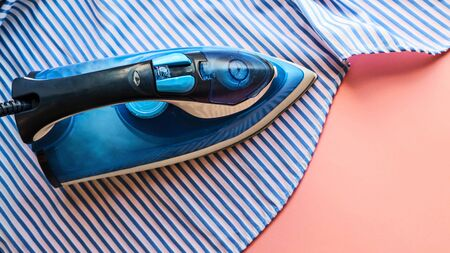 Photo pour Electric iron and shirt on ironing board in room on a pink background. iron blue striped shirt. - image libre de droit