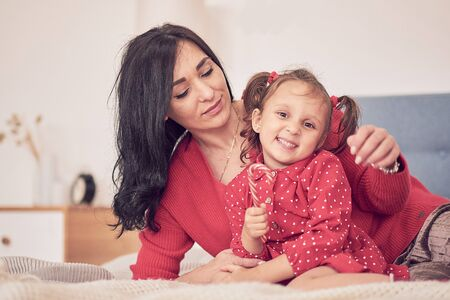 Foto de mom and daughter have fun together. a woman in a warm red knitted sweater hugs her little daughter in a red dress. family values - Imagen libre de derechos