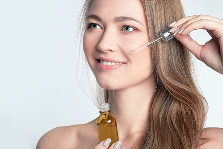 Photo pour beautiful model applying a skin serum treatment on white. Spa, skincare and wellness. Close up, copyspace - image libre de droit