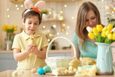 Photo pour Mother and son having fun together and celebrating feast. family getting ready for easter. Little and mom decorating home. soft focus - image libre de droit