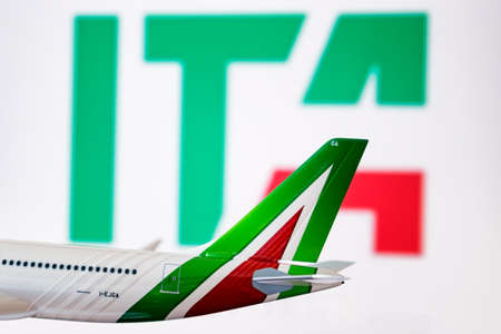 Foto per Cagliari, Italy, 27-08-2021. Logo of the new Italian flag carrier ITA. Old Alitalia livery passing in front of the new ITA company. Close up of Alitalia plane model with new ITA on background. - Immagine Royalty Free