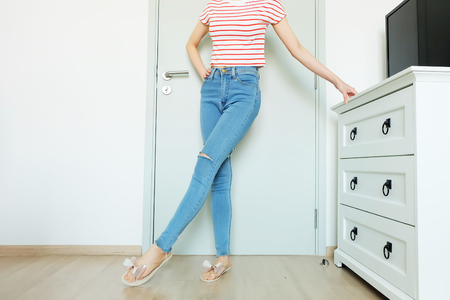 Summer Fashion Nude Bow Sandal (Footwear) and Slim Legs in The Room. Female Sexy Long Legs. Beautiful Slim Legs Woman Standing with Nude Sandals and Lack Blue Jean on Wooden Floor at Home Background