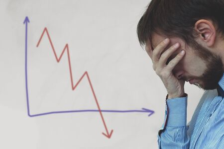 Photo pour Frustrated business man standing near white board in office, covers his face with his hand at the falling graph of a stock market struck in financial crisis - image libre de droit