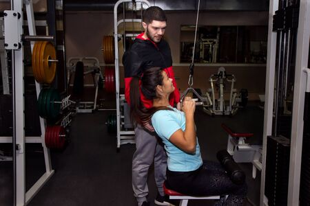 Photo for female with personal trainer doing pull ups on cable weight machine in cross fit training vintage fitness gym - Royalty Free Image