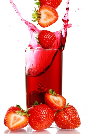 Strawberry falling into the glass with drink and makes big splashes