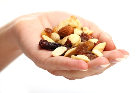 Hand with different dried fruits against white background