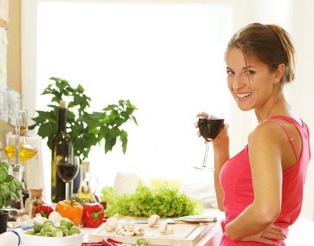 Woman drinking wine on the kitchen