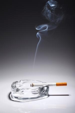 Cigarette in the ashtray over gray gradient