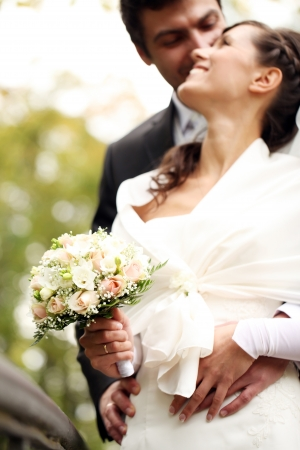 Close up of beautiful bride and happy groom in autumn park