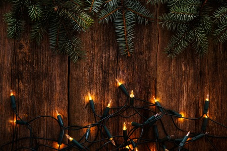 Christmas, New Year. Fir with garland on a wooden table
