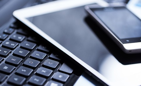 Closeup picture of a keyboard with a phone and tablet lying above it