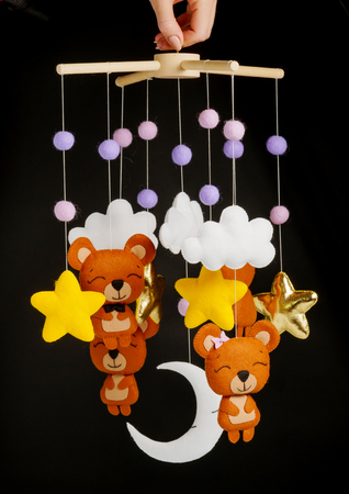 Photo pour Colorful and eco-friendly children's mobile from felt for children. It consists of bears, stars,moon, clouds and balloons toys. Handmade on black background. - image libre de droit