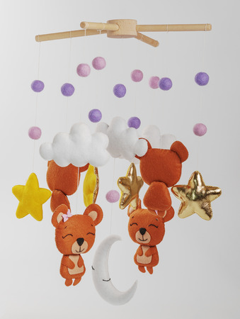Photo pour Colorful and eco-friendly children's mobile from felt for children. It consists of bears, stars,moon, clouds and balloons toys. Handmade on gray background. - image libre de droit
