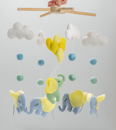 Photo pour Colorful and eco-friendly children's mobile from felt for children. It consists of elephant, clouds and balloons toys. Handmade on gray background. - image libre de droit