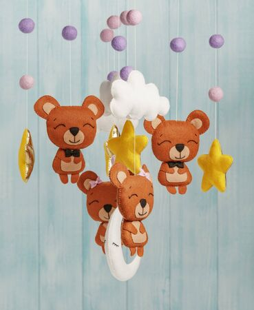 Photo pour Colorful and eco-friendly children's mobile from felt for children. It consists of bears, stars,moon, clouds and balloons toys. Handmade on blue background made from wood. - image libre de droit