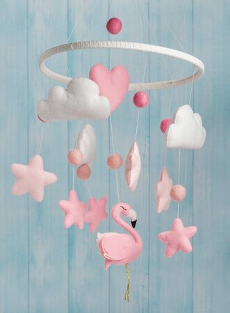 Photo pour Colorful and eco-friendly children's mobile from felt for children. It consists of flamingo toys, clouds, stars and balloons. Handmade on blue background made from wood. - image libre de droit