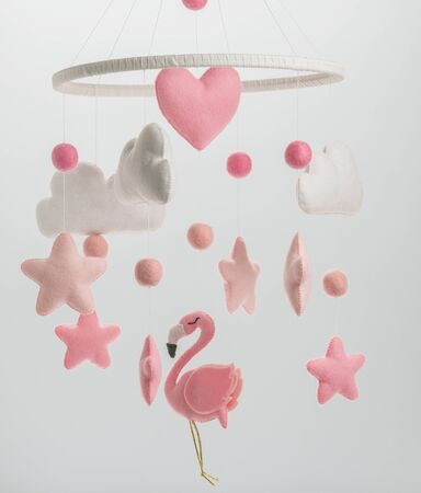 Photo pour Colorful and eco-friendly children's mobile from felt for children. It consists of flamingo toys, clouds, stars and balloons. Handmade on white background. - image libre de droit