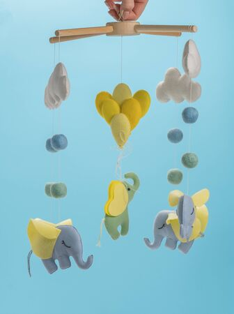 Photo pour Colorful and eco-friendly children's mobile from felt for children. It consists of elephant, clouds and balloons toys. Handmade on blue background. - image libre de droit