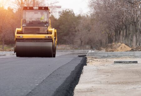 Photo for The vibratory roller levels the asphalt pavement. - Royalty Free Image