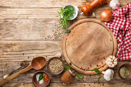 culinary background with empty cutting board and spices on wooden table
