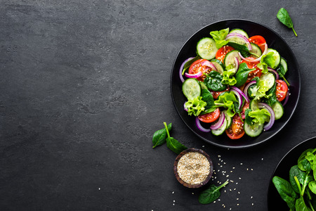 Photo pour Healthy vegetable salad of fresh tomato, cucumber, onion, spinach, lettuce and sesame on plate. Diet menu. Top view. - image libre de droit