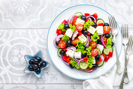Foto de Greek salad of fresh cucumber, tomato, sweet pepper, lettuce, red onion, feta cheese and olives with olive oil. Healthy vegetarian food - Imagen libre de derechos