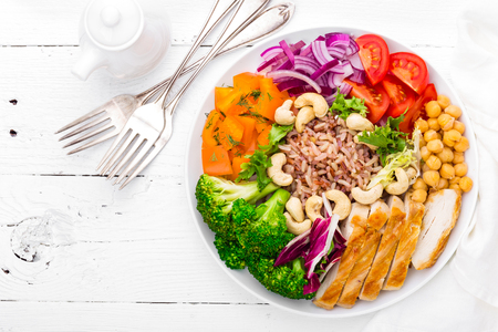 Photo for Buddha bowl dish with chicken fillet, brown rice, pepper, tomato, broccoli, onion, chickpea, fresh lettuce salad, cashew and walnuts. Healthy balanced eating. Top view. White background - Royalty Free Image