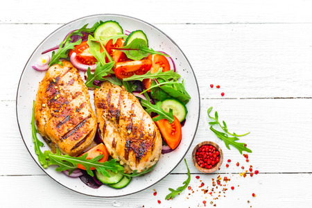 Photo pour Grilled chicken breast. Fried chicken fillet and fresh vegetable salad of tomatoes, cucumbers and arugula leaves. Chicken meat salad. Healthy food. Flat lay. Top view. White background - image libre de droit