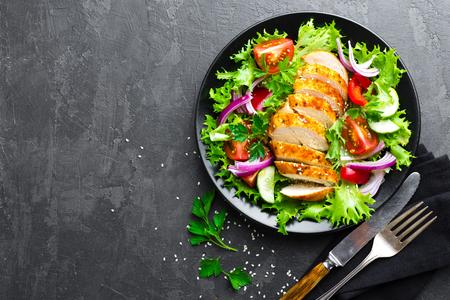 Foto de Salad with chicken meat. Fresh vegetable salad with chicken breast. Meat salad with chicken fillet and fresh vegetables on plate - Imagen libre de derechos