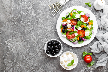 Photo pour Greek salad. Fresh vegetable salad with tomato, onion, cucumbers, basil, pepper, olives, lettuce and feta cheese. Greek salad on plate - image libre de droit