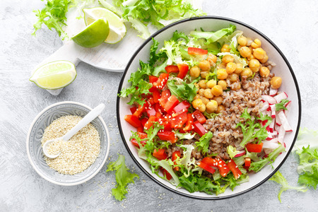 Photo pour Healthy and delicious bowl with buckwheat and salad of chickpea, fresh pepper and lettuce leaves. Dietary balanced plant-based food. Vegan and vegetarian dish. Top view. Flat lay - image libre de droit
