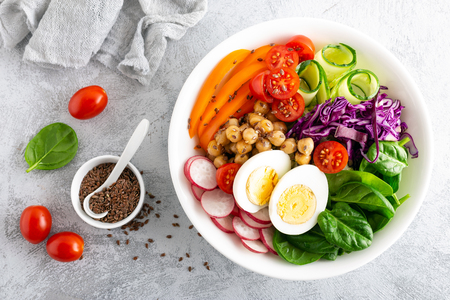 Buddha bowl salad with chickpeas, sweet pepper, tomato, cucumber, red cabbage kale, fresh radish, spinach leaves and boiled egg, healthy eating concept, top view, flat lay
