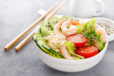 Foto de Hawaiian poke bowl with shrimps, rice and vegetables, healthy Buddha bowl with prawns, rice, avocado, cucumber, tomato and lettuce - Imagen libre de derechos